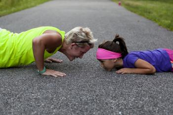 Woman and daughter doing push ups